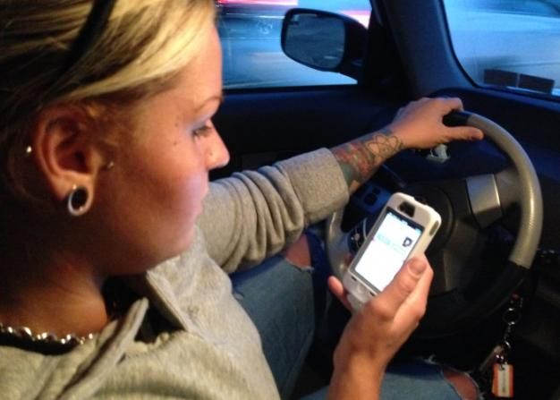 """Lyft driver Casey """"Redd"""" Gaspari at the end of a ride closes out the ..."""